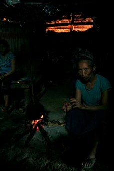 Grandma, the oldest of 3 generations living under one roof, sits with an opium pipe in northern Laos.