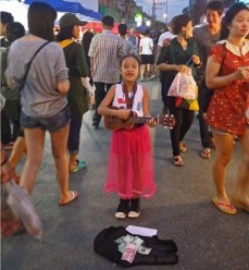 Little girls sings at Chiang Mai night markets, Thailand. Lucy Munday